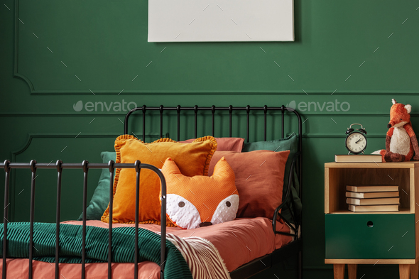 Orange pillow on single bed in dark green teenager bedroom - Stock Photo - Images
