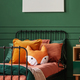 Orange pillow on single bed in dark green teenager bedroom - PhotoDune Item for Sale