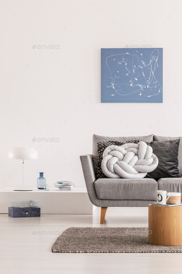 Trendy knot light grey pillow on comfortable scandinavian couch - Stock Photo - Images