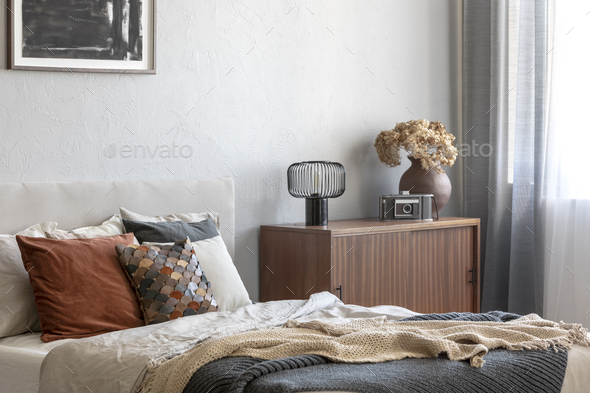 Vintage wooden cupboard next to king size bed with pillows and blanket in trendy bedroom interior - Stock Photo - Images