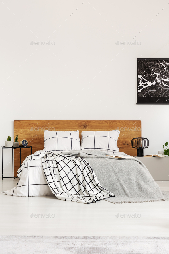 Black map on white wall above wooden headboard in simple bedroom interior - Stock Photo - Images
