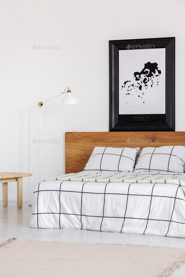 Black and white map in black frame in trendy bedroom interior with chequered bedroom - Stock Photo - Images