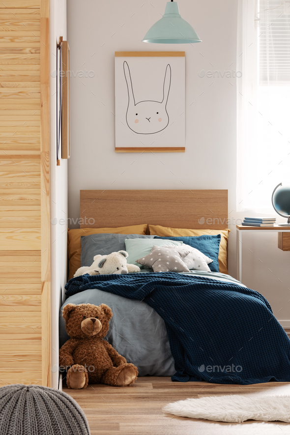 Brown cute teddy bear on wooden floor of stylish bedroom interior for kids - Stock Photo - Images