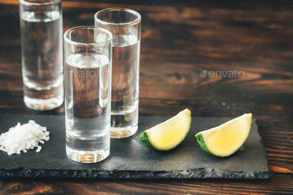 Glasses of tequila with lime wedges - Stock Photo - Images