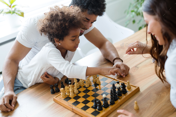 Happy family playing chess together - Stock Photo - Images