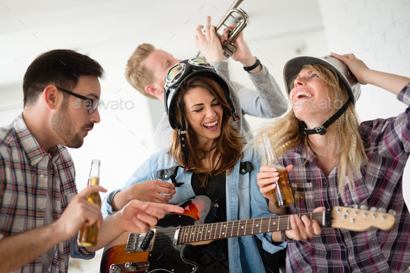 Friends having fun and partying in house and playing music - Stock Photo - Images