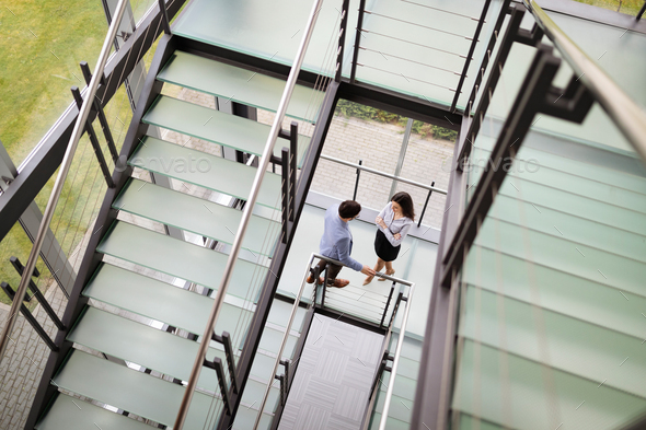 Modern business people walking on stairs in glass hall in office building - Stock Photo - Images