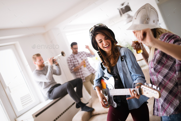 Group of friends playing guitar and partying at home - Stock Photo - Images