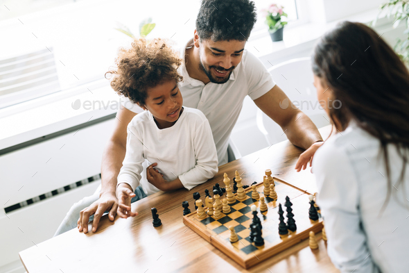 Happy family playing chess together at home - Stock Photo - Images