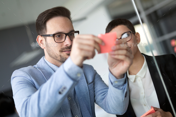 Creative business team looking at sticky notes on window - Stock Photo - Images