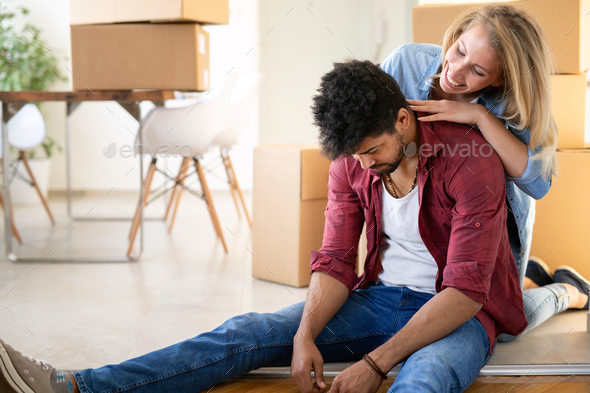 Tired couple with boxes moving into new home - Stock Photo - Images