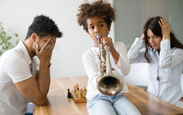 Mother and father trying to play chess while their child plays trumpet - Stock Photo - Images