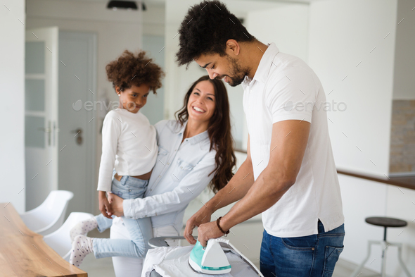 Young couple at home doing hosehold chores and ironing - Stock Photo - Images