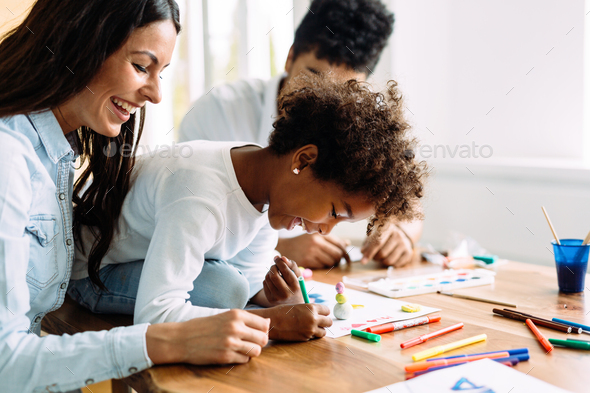Mother and father drawing together with their child - Stock Photo - Images