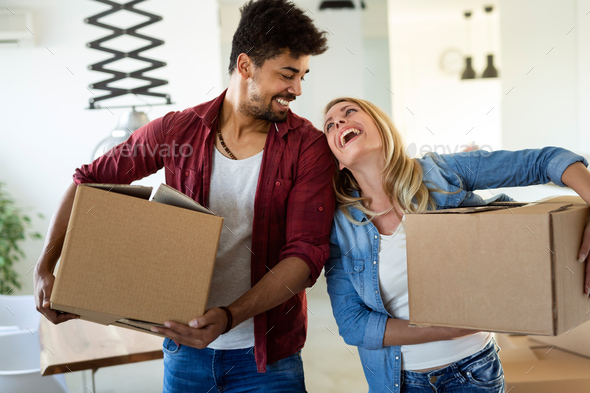 Young couple unpacking cardboard boxes at new home moving in concept - Stock Photo - Images