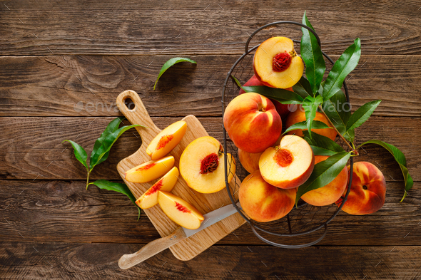 Ripe peaches with leaves in basket on wooden table, top view - Stock Photo - Images