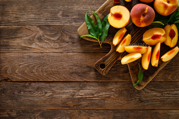 Ripe peaches with leaves on wooden board, top view - Stock Photo - Images