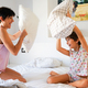 Mother and daughter having funny pillow fight on bed - PhotoDune Item for Sale