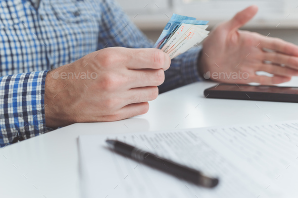 Tough financial conditions. Businessman holds money and gestures specifically - Stock Photo - Images