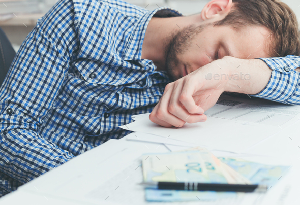 Overworked and tired businessman sleeping over at work on table in office - Stock Photo - Images