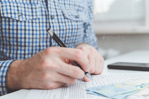 Man signing contract at office table - Stock Photo - Images