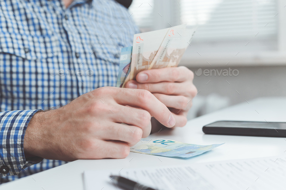 Businessman calculates the costs incurred or salary - Stock Photo - Images