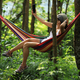 Woman relaxing in hammock and using smartphone in forest - PhotoDune Item for Sale