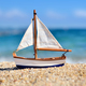 Miniature toy sailboat on the beach against the background of th - PhotoDune Item for Sale