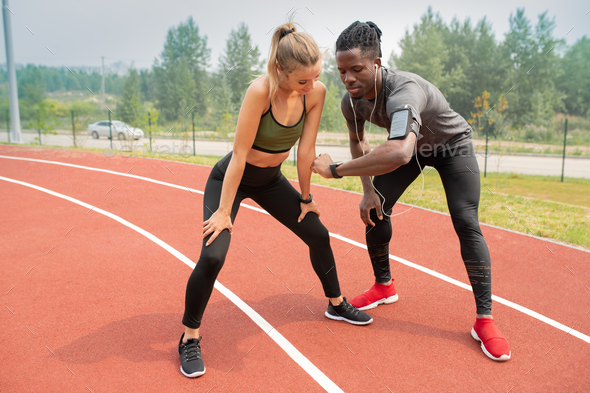 Young athlete showing time to active girl while both standing on start line - Stock Photo - Images
