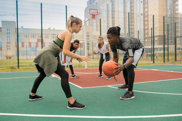 Young African man with ball and blonde sportswoman standing opposite each other - Stock Photo - Images