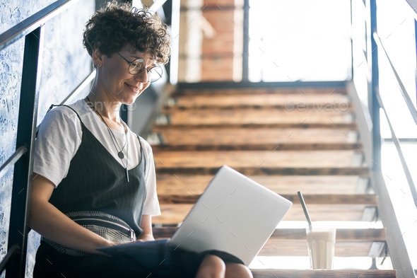Pretty designer in casualwear sitting on staircase with laptop on her knees - Stock Photo - Images