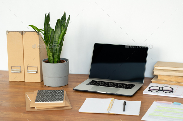 Workplace of office manager with laptop, potted plant, notebooks and books - Stock Photo - Images