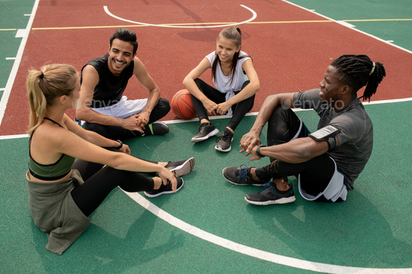 Happy young intercultural friends discussing last game of basketball - Stock Photo - Images