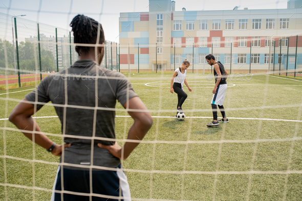 Rear view of young African sportsman standing by net and looking at two players - Stock Photo - Images