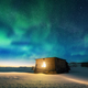 Aurora borealis over old small house with yellow light in window - PhotoDune Item for Sale