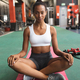 African-American woman sitting crosslegged on a yoga mat inside the a room at a sports center - PhotoDune Item for Sale
