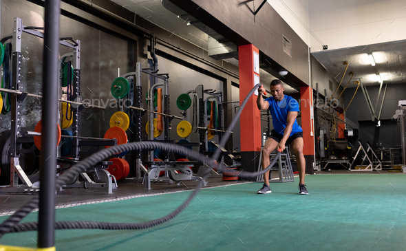 Front view of an African-American man doing battle rope exercises inside a room at a sports centre - Stock Photo - Images
