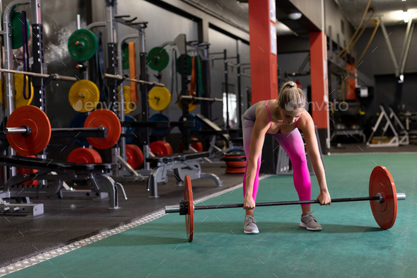 Front view of a Caucasian woman lifting weights inside a room at a sports centre - Stock Photo - Images