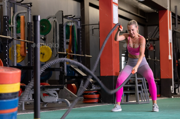 Front view of a Caucasian woman doing battle rope exercises inside a room at a sports centre - Stock Photo - Images