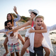 Group of friends having fun on the beach under sunset on vacation - PhotoDune Item for Sale
