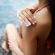 Close up photo of a young woman applying sunscreen protection cream - PhotoDune Item for Sale