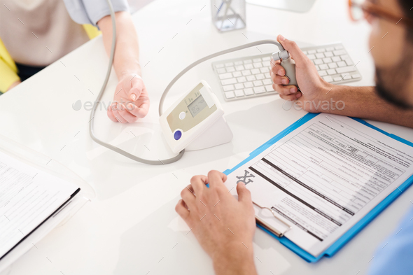 Doctor Measuring Blood Pressure - Stock Photo - Images