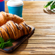 To Go breakfast croissant and coffee on wooden background , copy space - PhotoDune Item for Sale