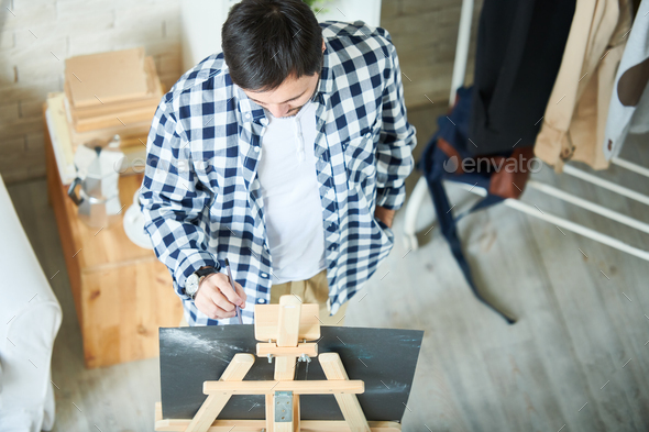 Casual man drawing at easel - Stock Photo - Images