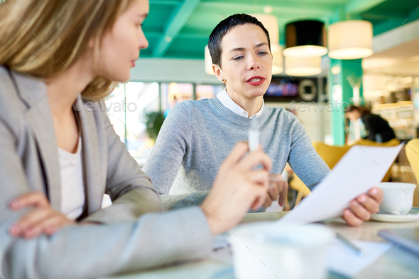 Two Business Women Reading Documents in Cafe - Stock Photo - Images