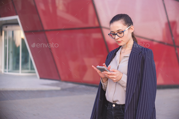 Young brunette woman in suit with smartphone - Stock Photo - Images