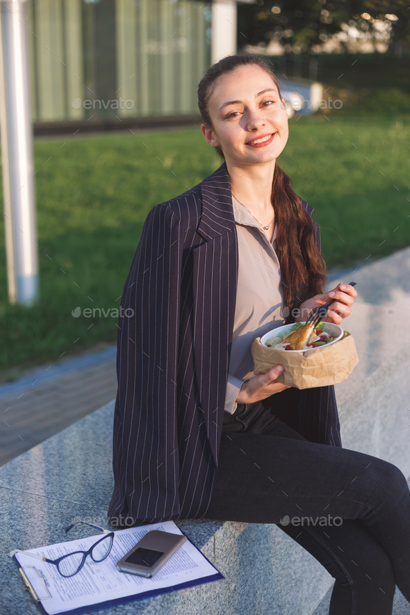 Young business woman eating salad on lunch break in city - Stock Photo - Images