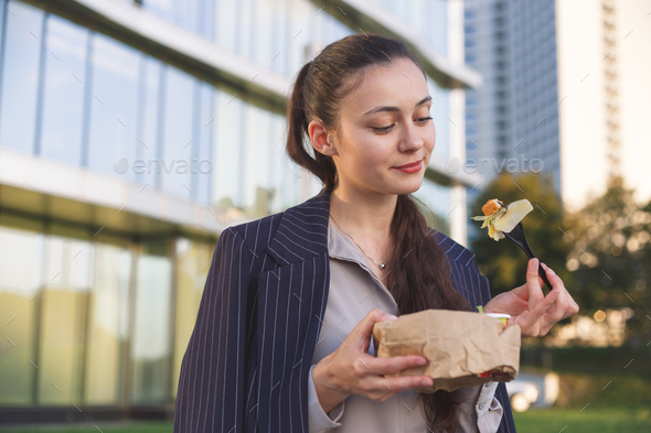Young busy woman enjoys salad sitting outdoor - Stock Photo - Images