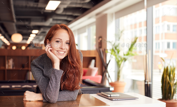 Portrait Of Casually Dressed Young Businesswoman Working At Desk In Modern Open Plan Workplace - Stock Photo - Images