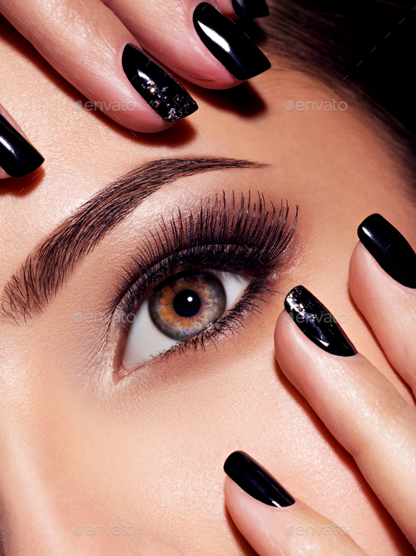Woman's eye with pink eye makeup and nails - Stock Photo - Images